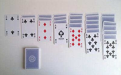 Na slici vidimo složene karte  ya Pasijans, Pauk ili Solitaire igru sa kartama.
